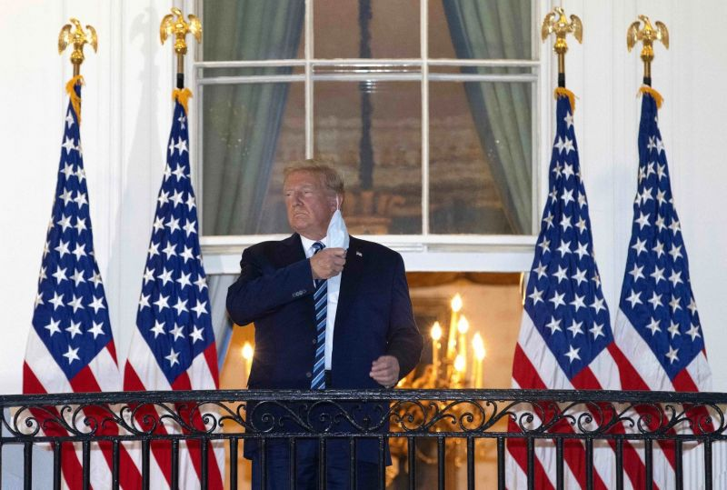 Donald Trump removes a face mask as he prepares to give an address at the White House