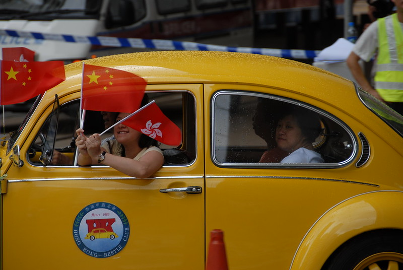 People ride in a vintage car flying Chinese and Hong Kong flags