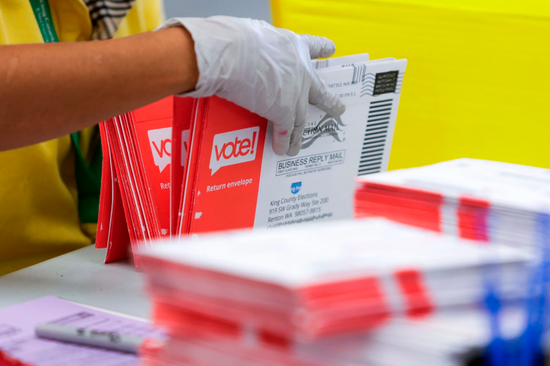 An official handles red and white postal vote envelopes