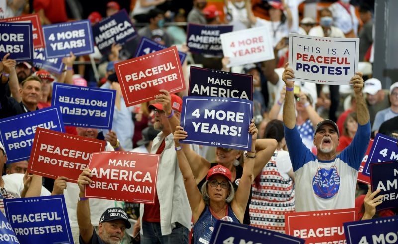 "Trump supporters hold signs that read ""4 more years"" and ""peaceful protester"""