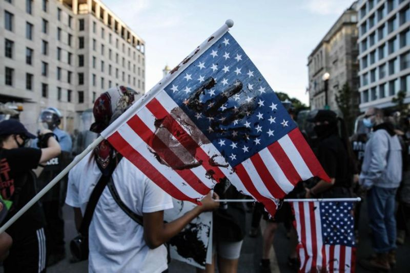Protesters stand with an American flag with a black hand painted on it
