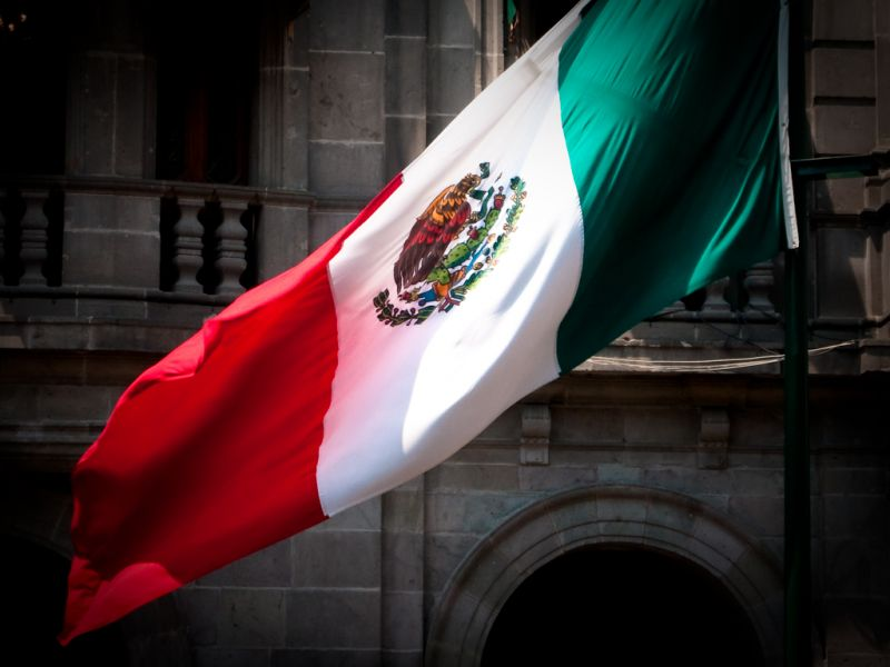 The Mexican flag flies in front of an old building