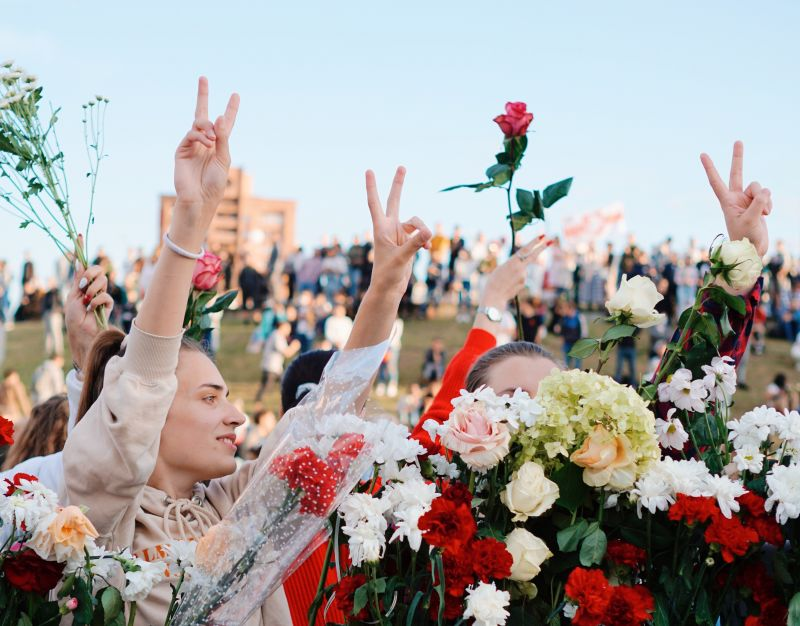 Female Belarusian protesters hold with flowers