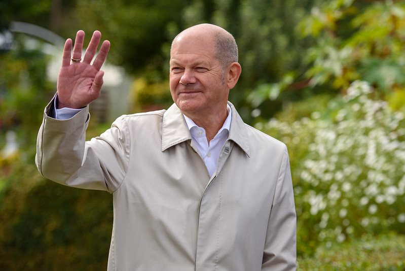 A man wearing a jacket and shirt waves while standing in a garden