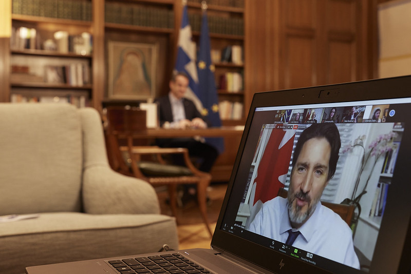 A laptop screen shows Justin Trudeau on Zoom