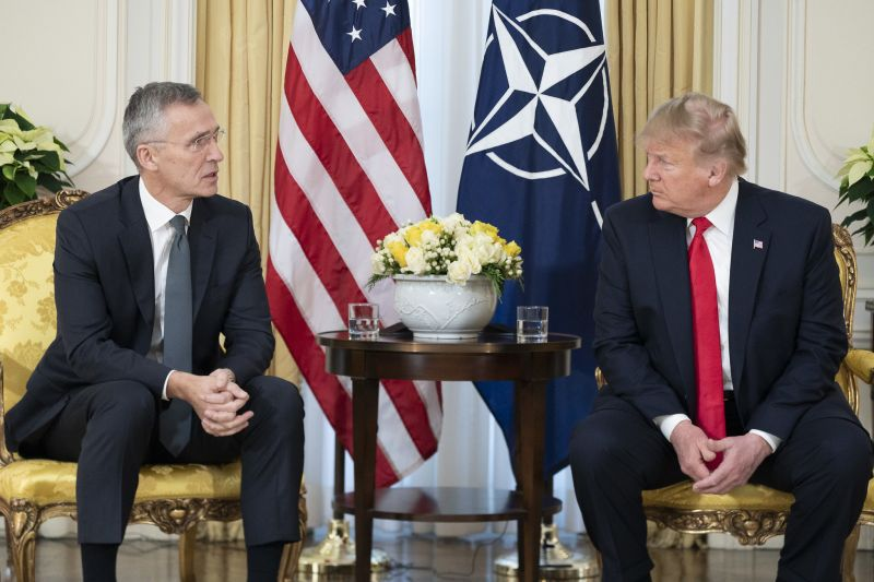 Donald Trump (right) meets with the Secretary of NATO next to a US and NATO flag