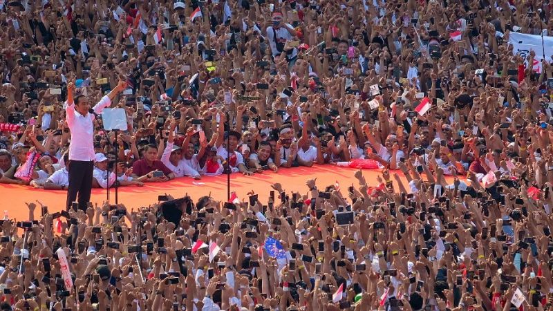 Joko Widodo puts his hands up at a campaign rally in Jakarta surrounded by crowds